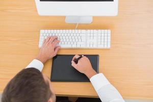 affärsman som arbetar med dator och digitaliserare på sitt kontor foto