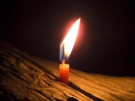 flamma av litet ljus på natten foto
