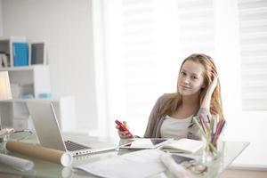 vacker ung kvinna på arbetsplatsen med sin telefon foto