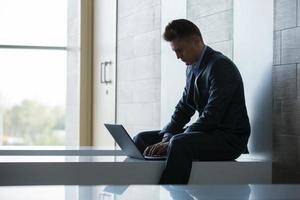 affärsman som sitter ensam på en bänk med bärbar dator foto