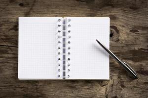 anteckningsbok och penna på trä bakgrund foto