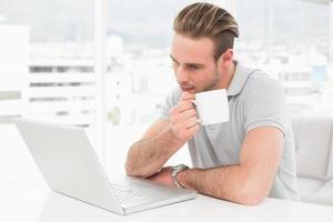 fokuserad affärsman som håller koppen medan du använder bärbar dator foto