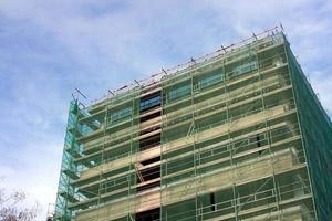 trappa och byggnadsställningar på en byggarbetsplats, täckt med nät. foto