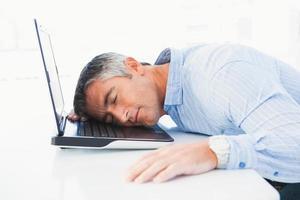 man med grått hår som sover på sin bärbara dator foto