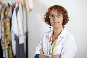 medelålders klädtillverkare som arbetar i sin verkstad foto