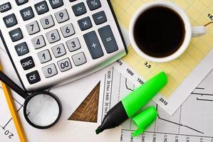 kaffe och räknemaskin på pappersbord med diagram foto