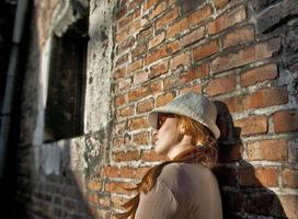 drömmer vacker kvinna med vit hatt i en romantisk gränd foto
