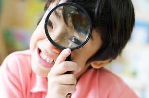 liten pojke med förstoringsglas på ögonen på nära håll