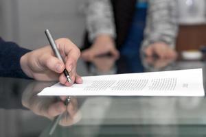 händerna på mannen undertecknar formellt papper, kvinnliga händer på bakgrund foto