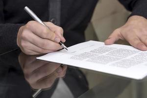 händerna på mannen underteckna formellt papper foto