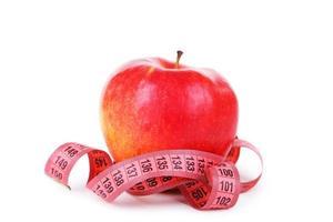 rött äpple med måttband isolerad på vitt foto