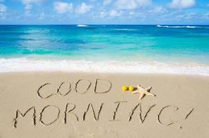 """underteckna """"god morgon"""" på stranden foto"""