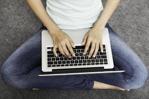 ung kvinna sitter medan du använder laptop foto