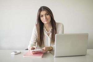 glad ung vacker kvinna som använder bärbara datorer, inomhus foto