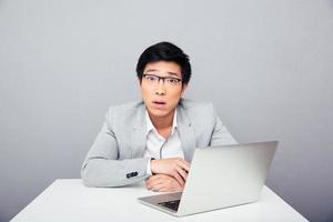 förvånad affärsman som sitter vid bordet med laptop foto