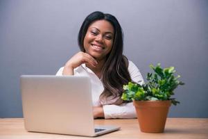 affärskvinna som sitter vid bordet med laptop foto