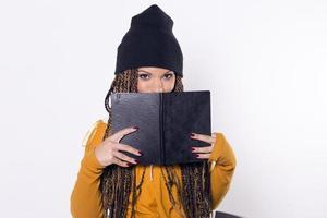 kvinna som ler, gömmer sig bakom en svart bok