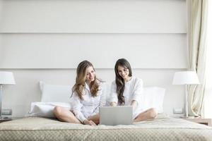 kvinnor i sängen med laptop foto