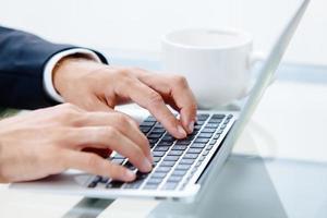 mans händer på tangentbordet på den bärbara datorn foto