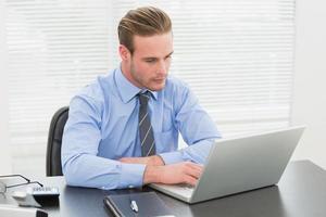 koncentrerad affärsman som använder sin bärbara dator foto