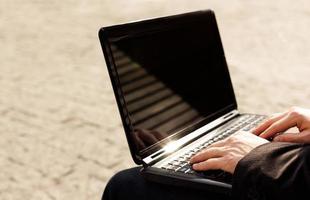 man skriver på sin bärbara dator. foto
