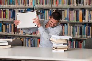 frustrerad student som kastar sin bärbara dator foto