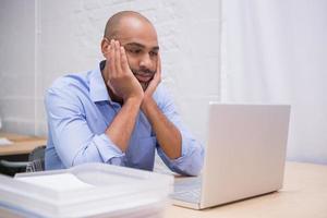 affärsman som använder bärbar dator vid skrivbordet foto