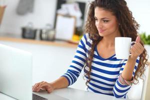 le ung kvinna med kaffekopp och bärbar dator i foto