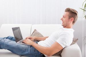 ung man använder bärbar dator foto