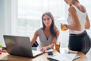 ung affärskvinna som sitter vid skrivbordets främre bärbara dator med henne foto