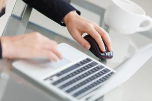 kvinnans händer på tangentbordet på laptop foto