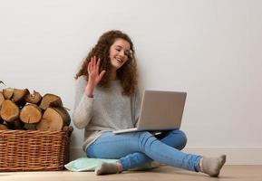 tonårsflicka som använder bärbar dator och vinkar hej på chatten foto