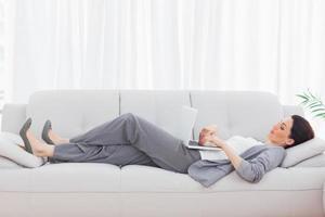 affärskvinna som använder sin bärbara dator som ligger på soffan foto