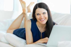 ung kvinna som använder en bärbar dator medan du kopplar av hemma foto