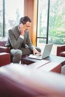 glad man pratar i telefon med sin bärbara dator