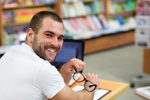 porträtt av en man med glasögon i bokhandeln foto
