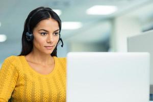 affärskvinna i hörlurar med bärbar dator foto