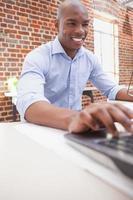 avslappnad affärsman som använder sin bärbara dator vid skrivbordet foto
