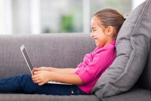 liten flicka som använder bärbar dator på soffan foto