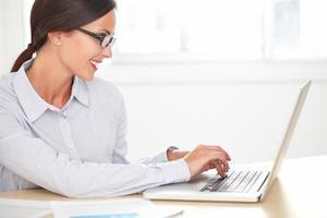 latin affärskvinna leende medan du arbetar på skrivbordet foto