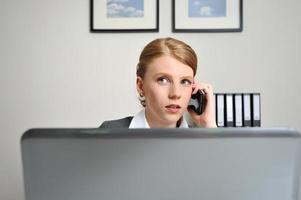 kvinna i telefonen bakom en dator foto