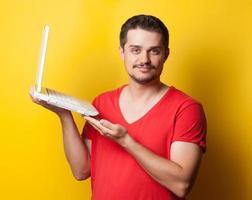 kille i t-shirt med bärbar dator foto