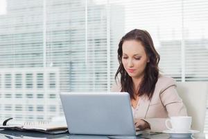 koncentrerad affärskvinna som arbetar på sin bärbara dator foto