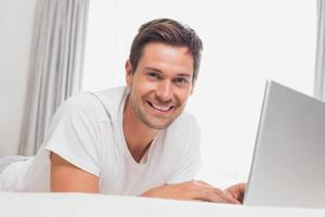 porträtt av avslappnad casual man använder bärbar dator i sängen foto