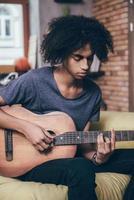 spelar gitarr. foto