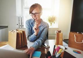 ung kvinna som arbetar hemma, litet kontor foto