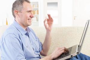 döv man använder teckenspråk med bärbar dator foto