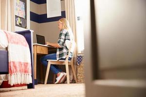 flicka sitter vid ett skrivbord i hennes sovrum med laptop foto