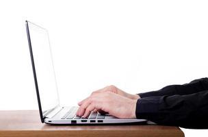 mans fingrar på tangentbordet på den bärbara datorn foto