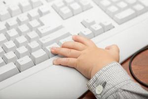 hand av liten pojkebarn på datortangentbordet foto